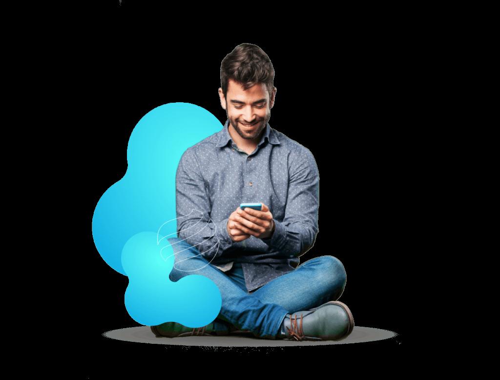 Homem sentado mexendo em um celular.